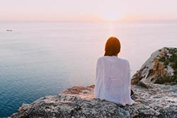 A woman sitting facing the sea during sunrise can be a sign of depression