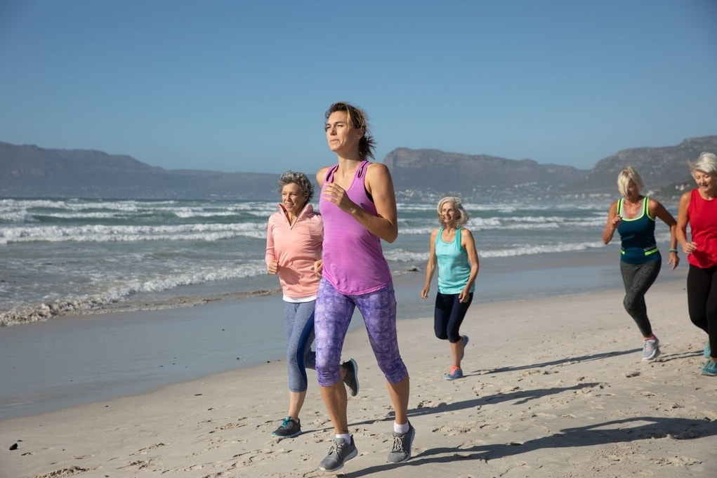 A group of women running in the beach after a successful breast cancer screening