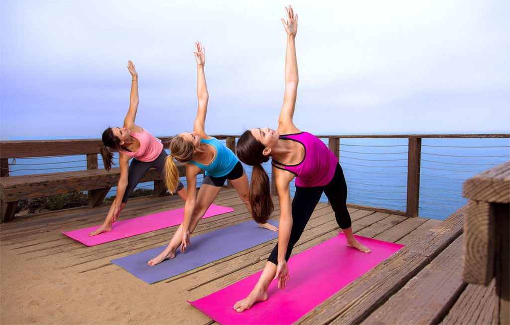 Three young women practicing Yin Yoga on oceanfront